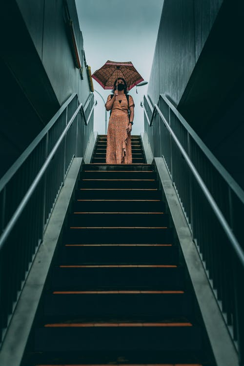 From below full body female wearing maxi dress and protective face mask standing with umbrella on street staircase on overcast weather