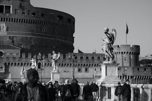 Black and white crowd of diverse travelers walking on bridge with marble statues near famous ancient Castel Sant Angelo on sunny day in Rome