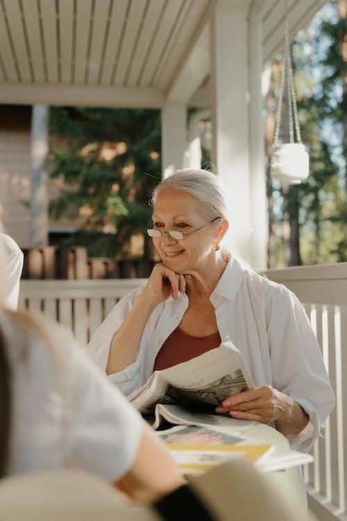 Elderly Woman in White Dress Shirt Holding A Newspaper