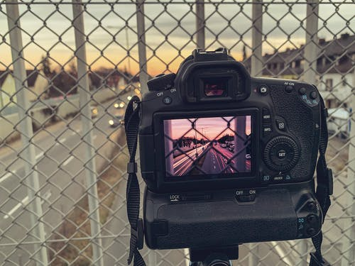 Black Dslr Camera on Black Metal Fence