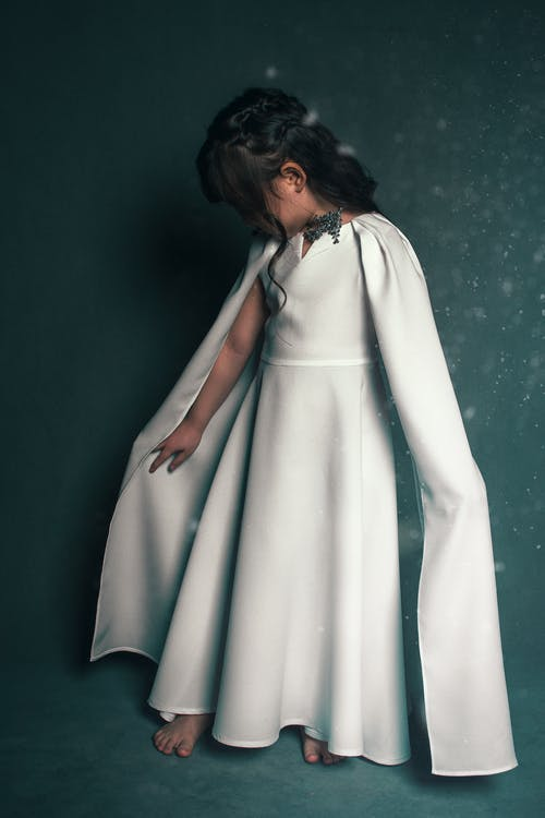 Charming little kid standing barefoot while wearing classy white dress with silk cape against blue background