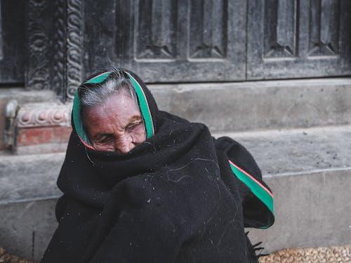 Unhappy senior ethnic woman in warm fabric on street