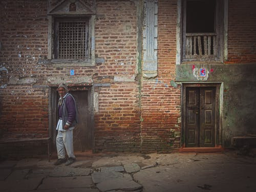 Side view of bearded senior ethnic male looking at camera on rough walkway near old brick building in town