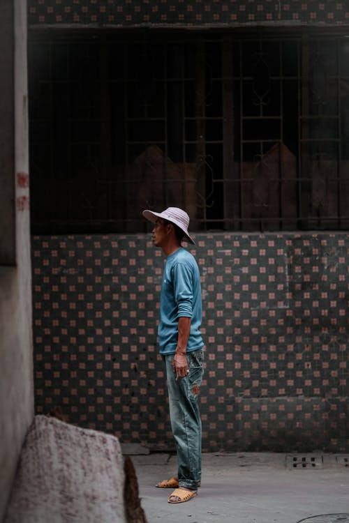 Attentive ethnic man in hat near old building