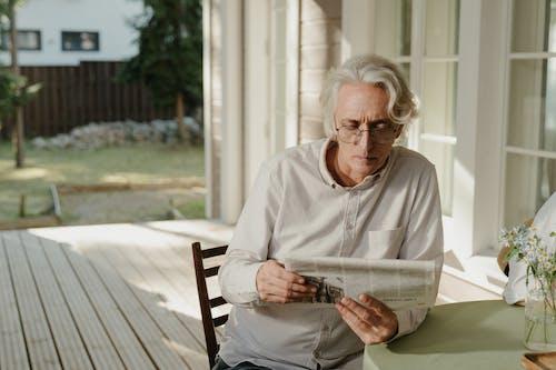 Elderly Man in White Crew Neck Dress Shirt Reading Newspaper