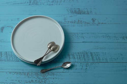 White Ceramic Plates With Teaspoons On Blue Wooden Surface