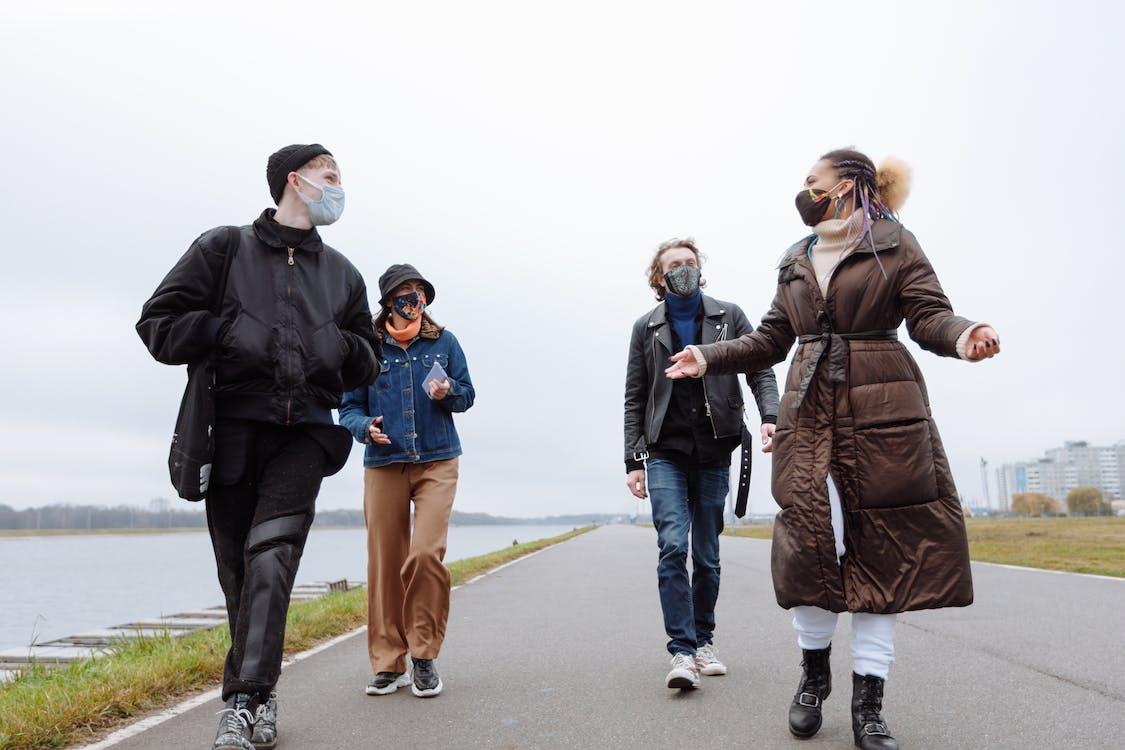 3 Women and 2 Men Standing on Gray Asphalt Road