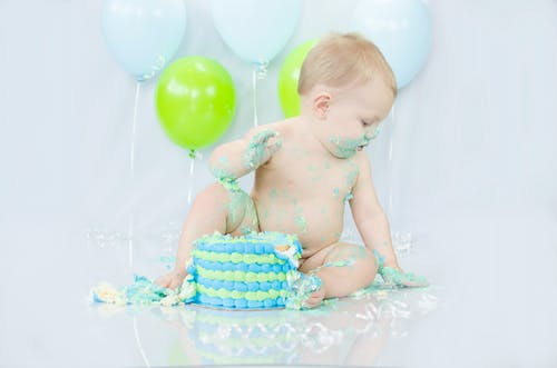 Baby in Blue and White Polka Dot Shorts Sitting on White and Blue Polka Dot Inflatable