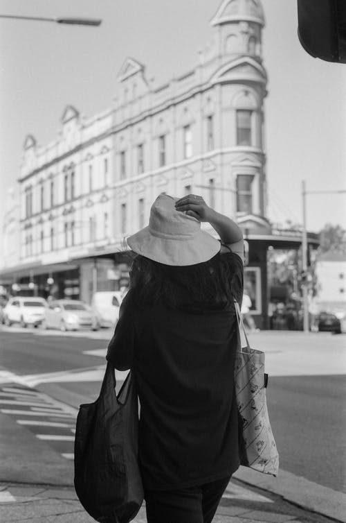 Woman in hat with bags walking on street