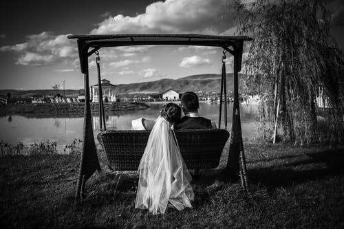 Black and white of peaceful bride in veil leaning on shoulder of groom sitting on swings on coast of calm lake