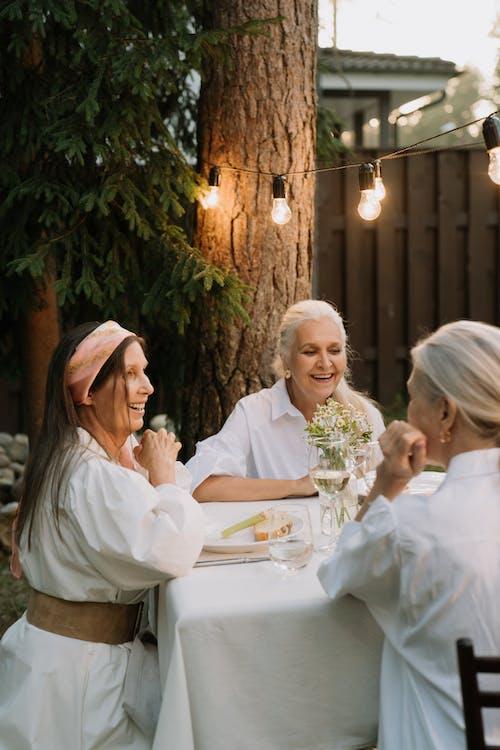 白い長袖シャツの女性の横に座っている白い長袖シャツの女性