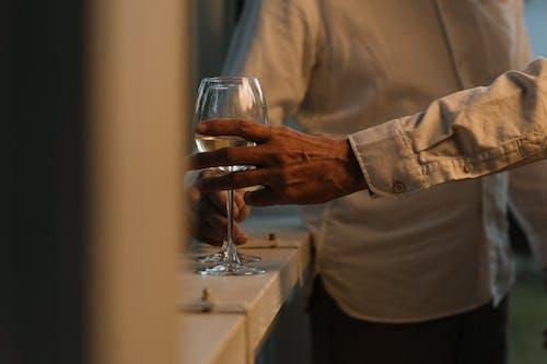 Hombre En Camisa De Vestir Beige Sosteniendo Una Copa De Vino Clara