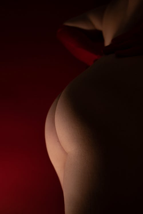 Side view of anonymous provocative female with naked booty standing on red background with low light in studio with alluring body curves
