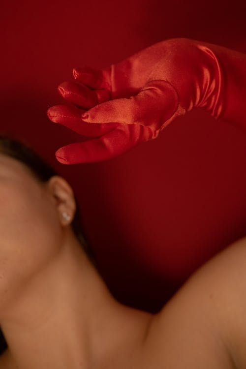 Unrecognizable female with bare shoulder wearing glove on raised hand standing with tilted head on red background in modern studio