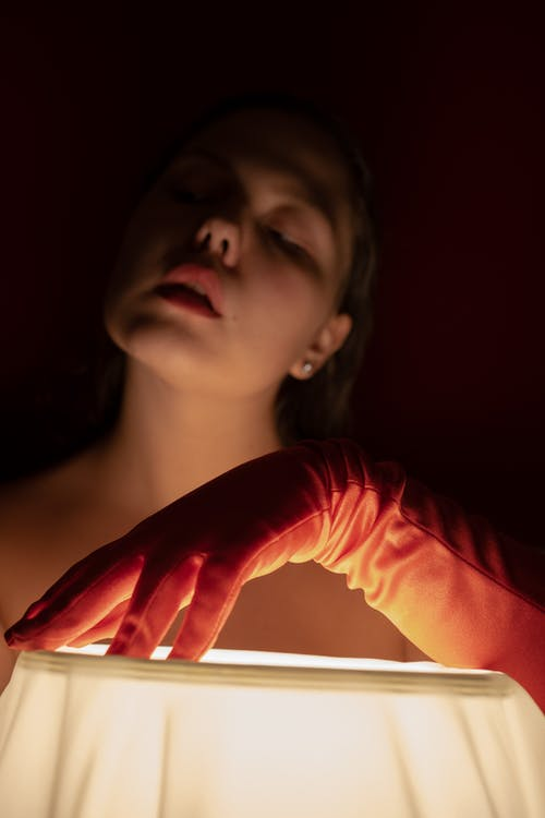 Dreamy female with tilted head wearing red glove while standing in dark room with hand on glowing lamp in studio