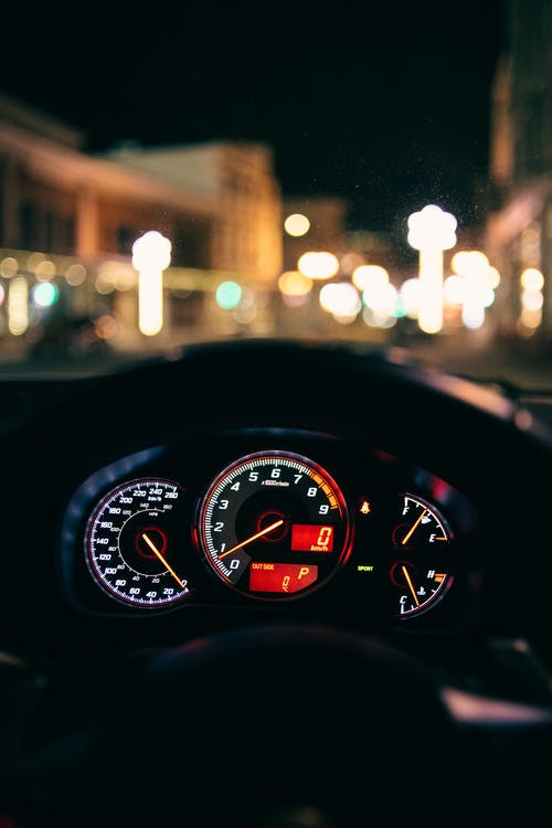 Glowing dashboard of modern car driving in illuminated city street