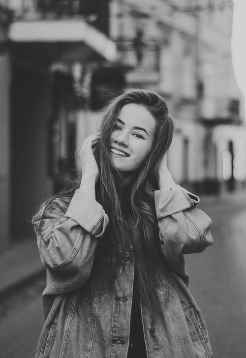 Grayscale Photo of Smiling Woman Looking at Camera