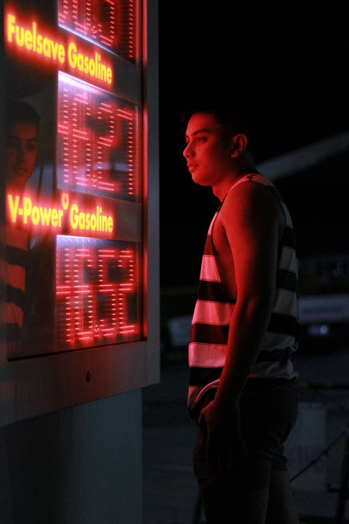 Side view of young ethnic in casual clothes standing near electronic price board of modern gas station in city at night