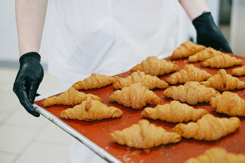 Person Holding a Tray of Freshly Baked Croissant