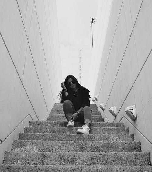 Woman in Black Long Sleeve Shirt Sitting on Concrete Stairs