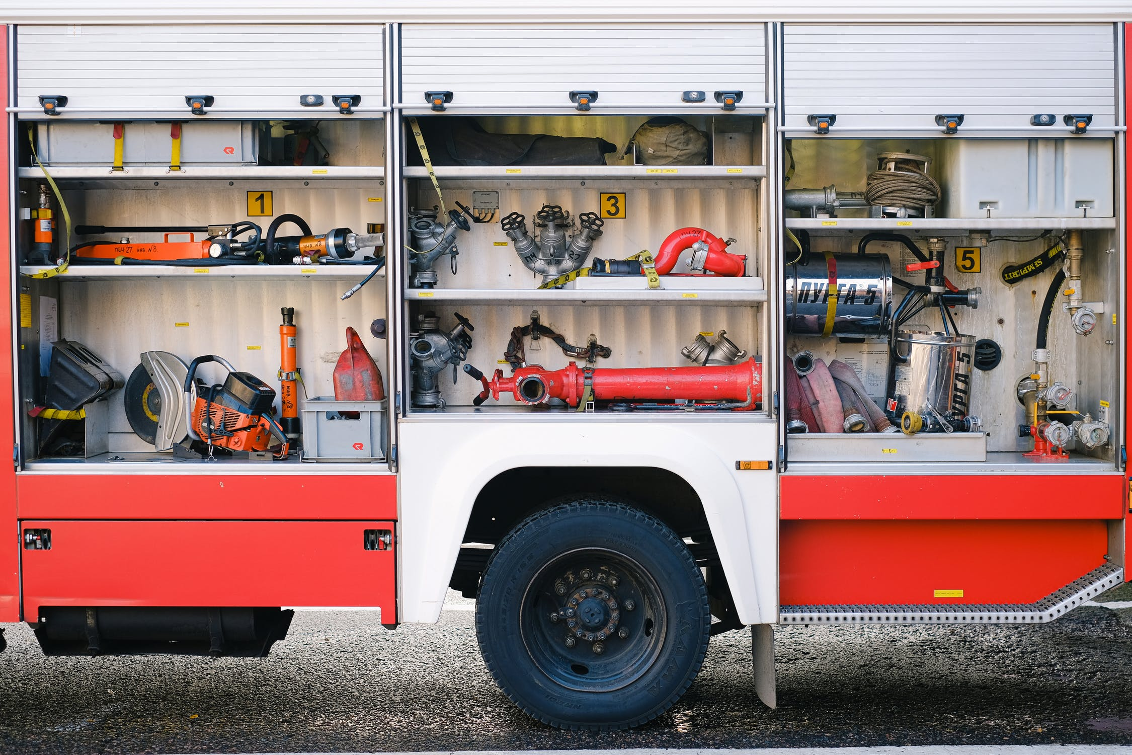 The cargo compartment of a firetruck displaying many emergency tools on shelves.