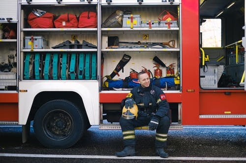 Man Smiling while Sitting on Running Board of a Fire Truck