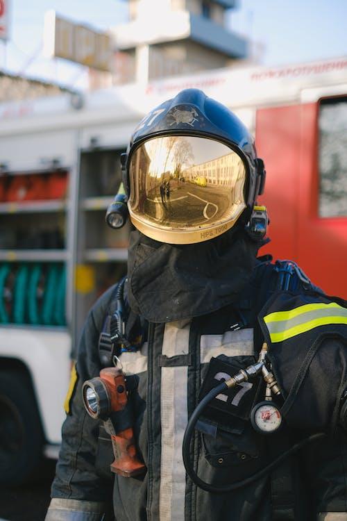 A Firefighter in Uniform Standing Near a Fire Truck