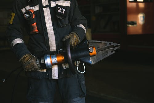 Man in Black Jacket Holding Gray and Black Power Tool