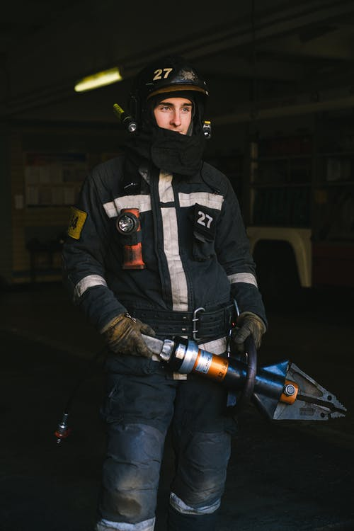 Man in Black and Gray Jacket Holding Black and Gray Power Tool