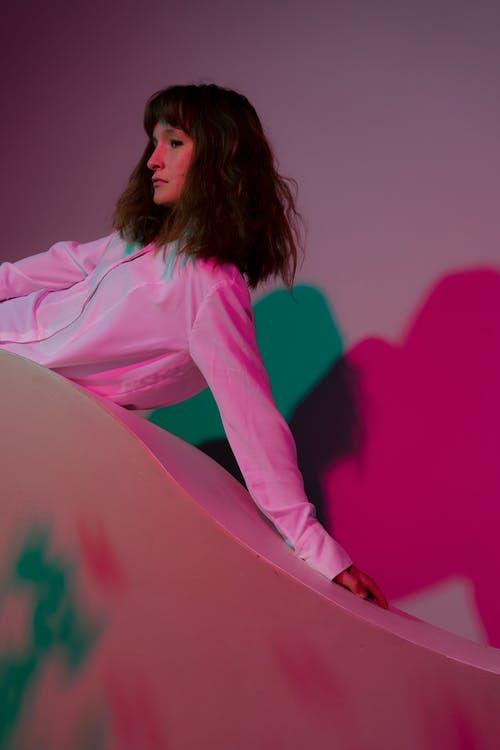 Emotionless woman lying on stand in pink lights
