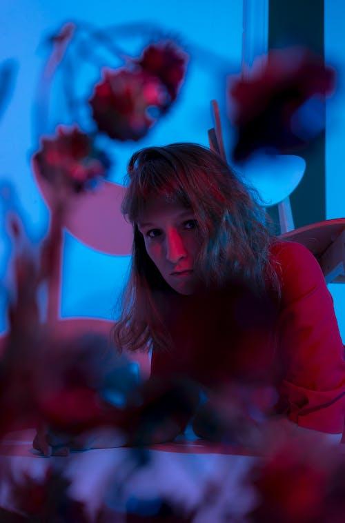 Serious woman lying on floor in dark room