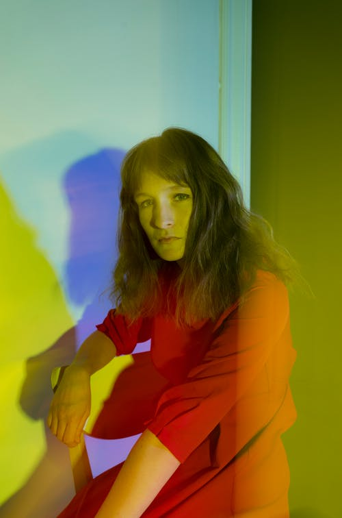 Serious woman sitting on chair in yellow light in room
