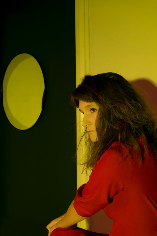 Side view thoughtful adult female in red dress sitting in dark room in yellow light and looking away pensively