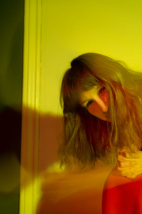 Content woman leaning forward in yellow lights in room