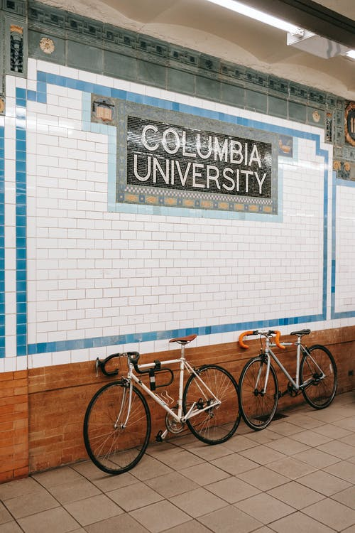 Bikes parked near stone decorated wall of Columbia University underground station in New York