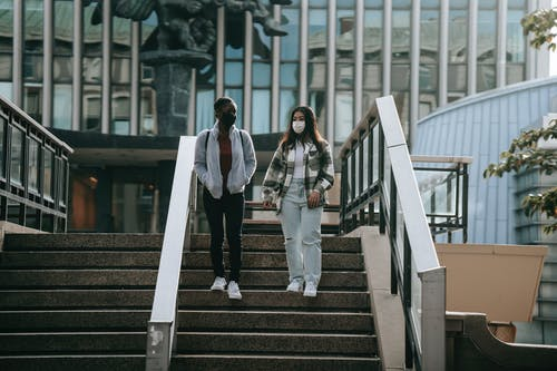 Full body young multiracial female students in casual outfits and protective masks going down stairs and talking in university campus