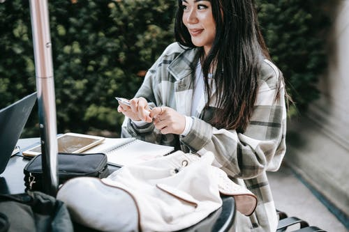 Positive young Asian female student in checkered shirt sitting at table in campus and taking notes while doing home task