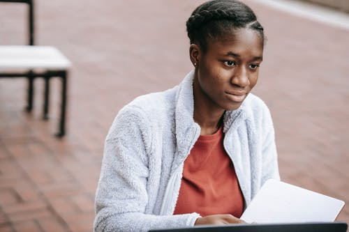 High angle of calm young African American female student with opened notepad sitting at table in campus while doing home task