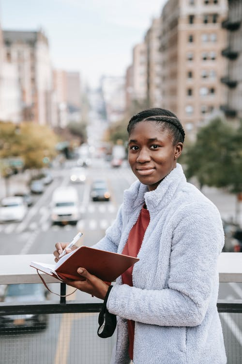 Delighted young African American female student looking at camera while standing on footbridge over road and taking notes in notepad