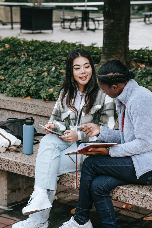 Content diverse students with smartphone and diary interacting in town