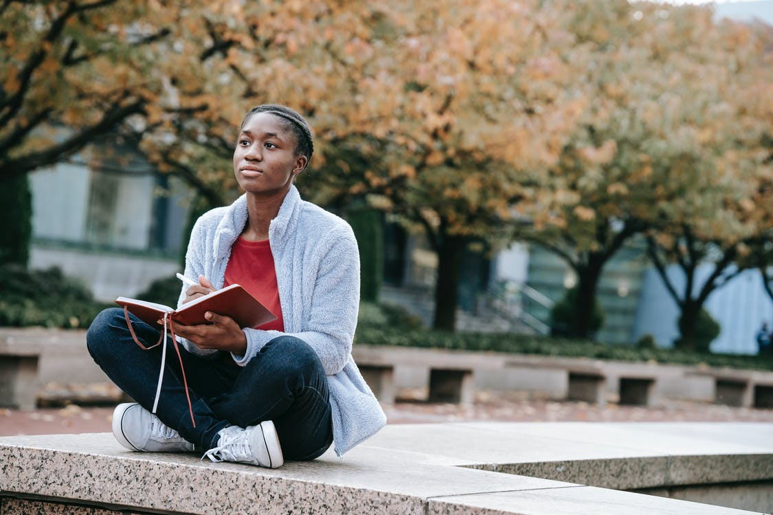 Young contemplative African American woman with agenda sitting with crossed legs against autumn trees while looking forward in city