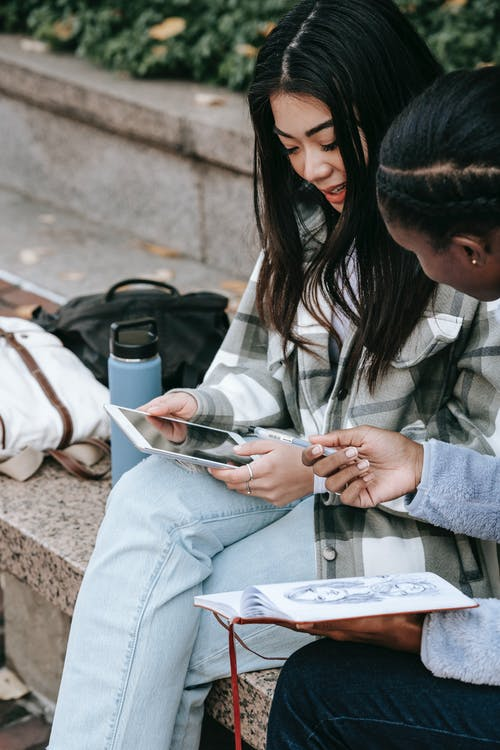 Crop young Asian woman showing cellphone with black screen to unrecognizable ethnic female friend while talking on city bench