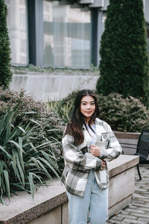 緑の植物の近くに立っている白いコートの女性