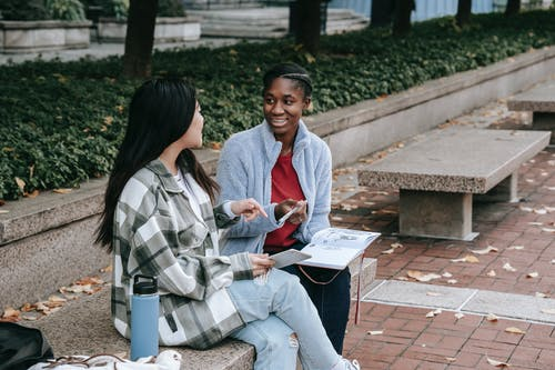 Happy black woman talking to unrecognizable girlfriend on city bench
