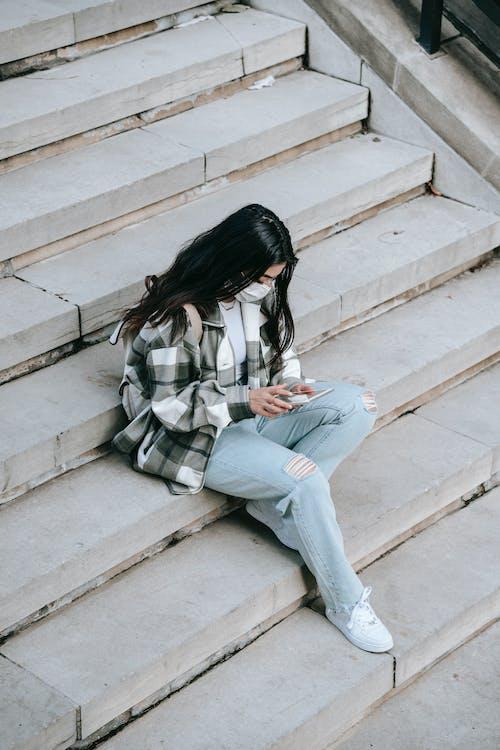 Wanita Dengan Kemeja Lengan Panjang Kotak Kotak Putih Dan Hitam Dan Jeans Denim Biru Duduk Di Atas Beton