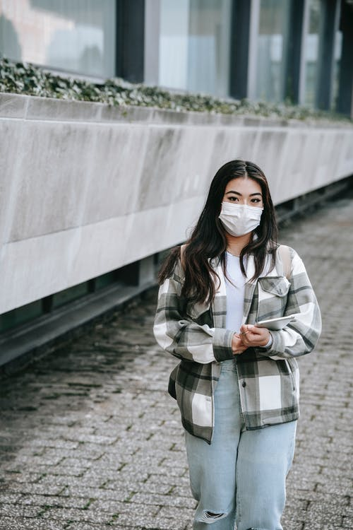 Anonymous millennial ethnic woman with smartphone on urban pavement