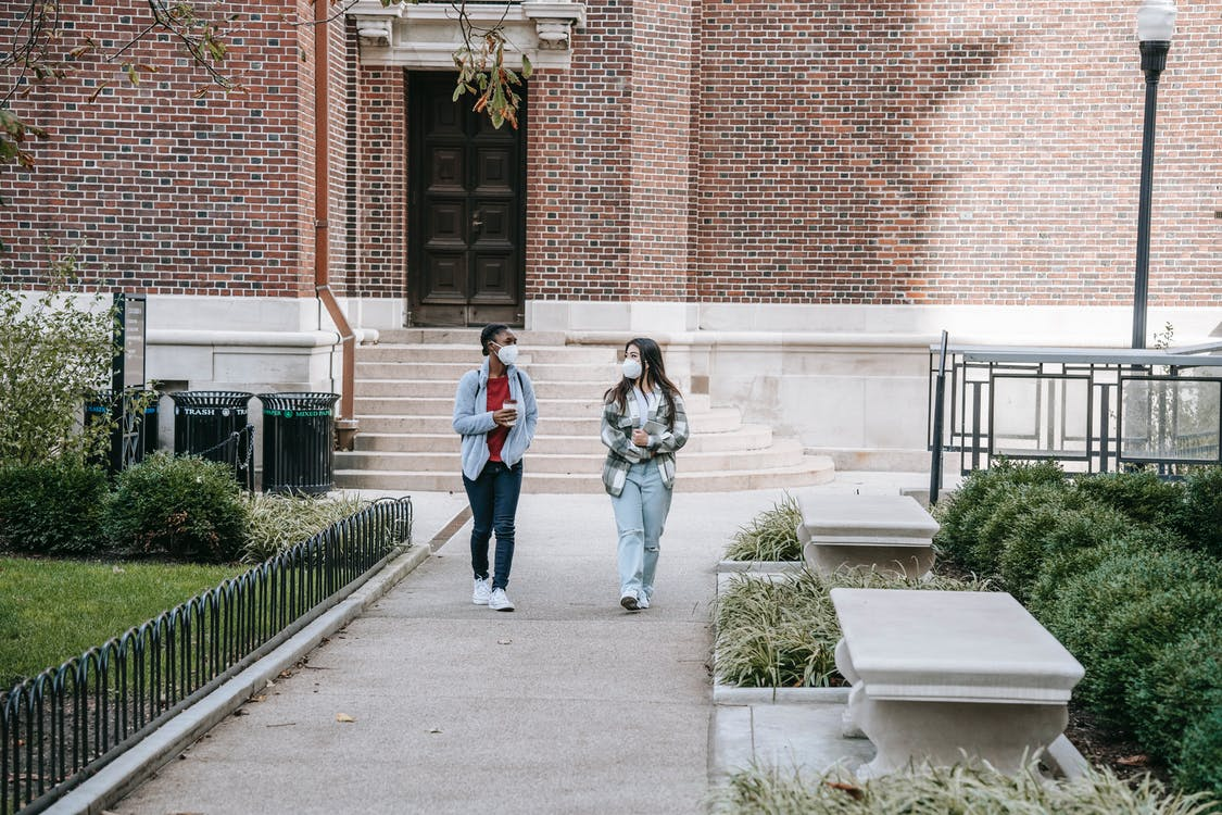 Full body of young multiethnic female students in casual clothes and medical masks walking in campus park after lessons