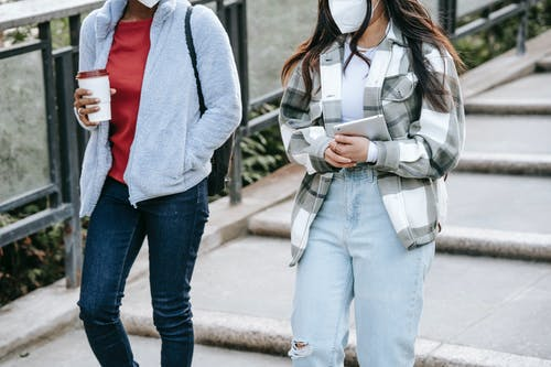 Anonymous female teens walking in park with takeaway coffee and tablet in hands