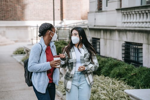 Positive young multiracial female best friends in casual clothes and face masks chatting while standing on street with takeaway coffee and tablet before studies