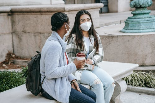 Multiethnic girlfriends sitting in street in masks
